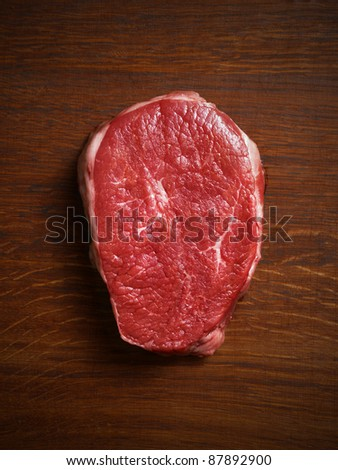 Raw steak on the wooden board. - stock photo