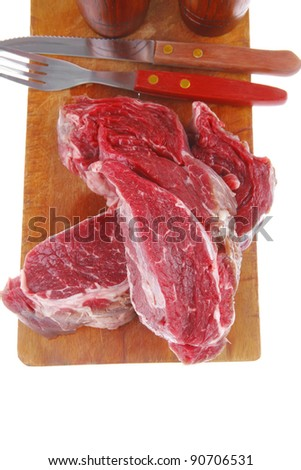 raw steak ready to prepare on cut board with cutlery and castor - stock photo