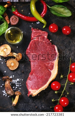 Raw steak served with vegetables and forest mushrooms on black metal cutting board over old wooden table. See series - stock photo