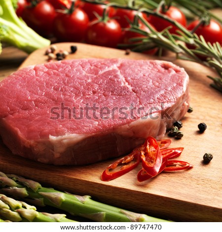 Raw Steak with green asparagus on wooden board - stock photo