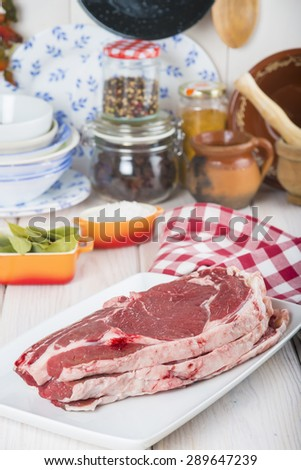 Raw steaks on the kitchen table ready to cook - stock photo