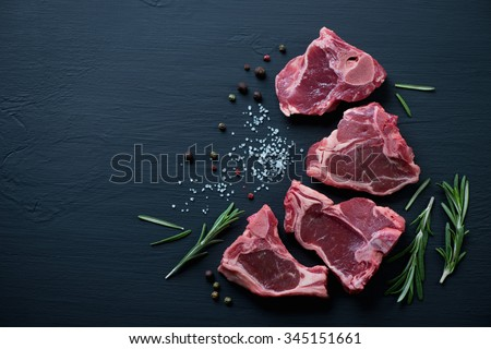 Raw T-bone lamb steaks with seasonings on a black wooden surface - stock photo