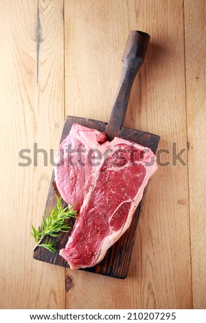 Raw t-bone or porterhouse steak with a sprig of fresh rosemary on a vintage wooden board , overhead view on wood with copyspace - stock photo