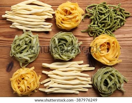 Raw tagliatelle pasta on the wooden table. - stock photo
