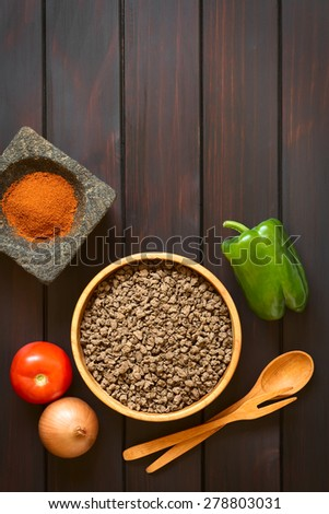 Raw textured vegetable or soy protein, called also soy meat in wooden bowl with raw vegetables and paprika in mortar. Photographed overhead on dark wood with natural light.  - stock photo
