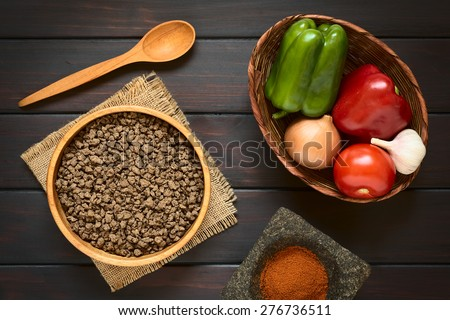 Raw textured vegetable or soy protein, called also soy meat in wooden bowl with raw vegetables in basket and paprika in mortar. Photographed overhead on dark wood with natural light.  - stock photo