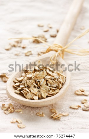 Raw thick rolled oats in a wooden spoon. - stock photo