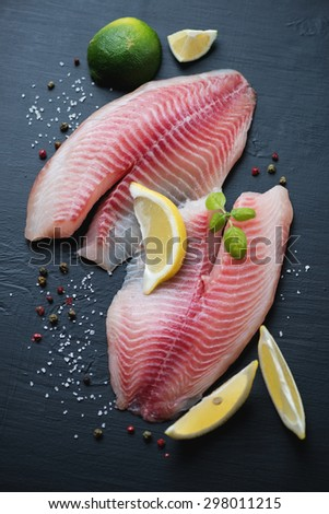 Raw tilapia with seasonings, black wooden background, above view - stock photo