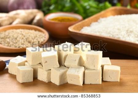 Raw tofu cut in dices on wooden board with rice and other raw ingredients in the back (Selective Focus, Focus on the front of the tofu) - stock photo