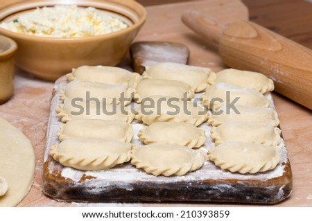 Raw traditional Ukrainian hand-made varenyky (Dumplings, pierogi ruskie in Poland) with cottage cheese - stock photo