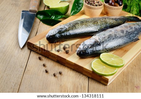 Raw trout on the chopping board with limes - stock photo