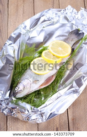 Raw trout with dill and lemon slices - stock photo