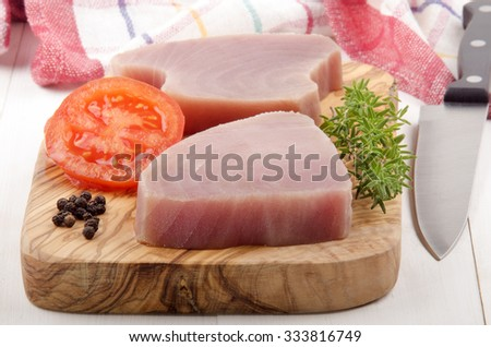 raw tuna fillet with thyme, tomato and pepper on a wooden board - stock photo