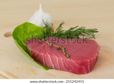 Raw tuna steak with rosemary and thyme - stock photo