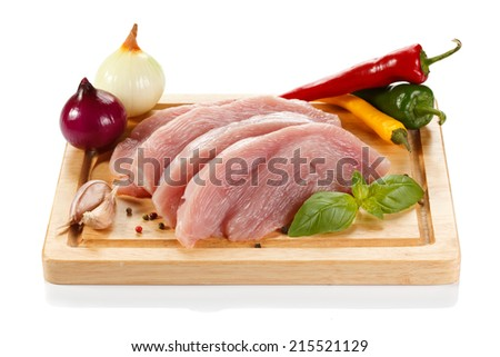 Raw turkey fillets on cutting board and vegetables - stock photo