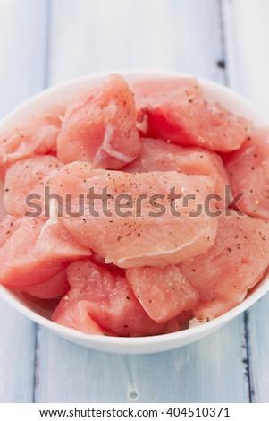 raw turkey on white dish on blue background - stock photo