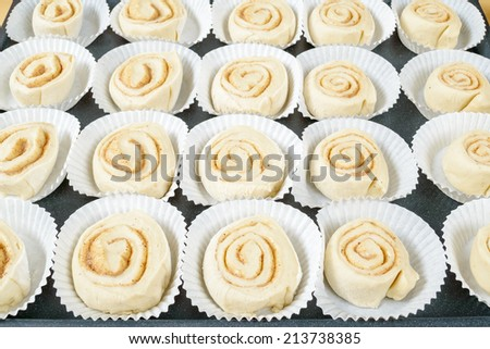 Raw, unbaked buns in disposable paper baking cups. - stock photo