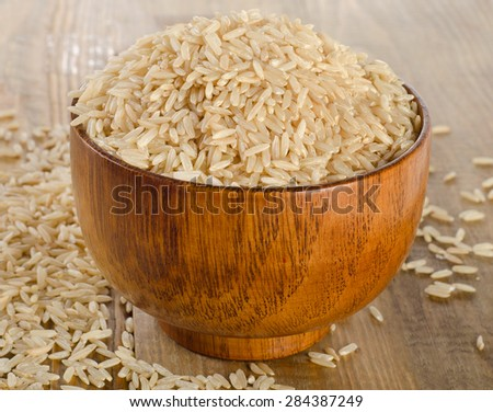 Raw uncooked brown rice in wooden bowl. Selective focus - stock photo