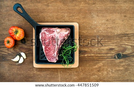 Raw uncooked meat t-bone steak with garlic cloves, tomatoes, rosemary in small dark cooking pan over rustic wooden background, top view, copy space, horizontal composition - stock photo