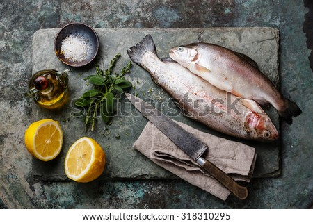 Raw uncooked Trout fish with spices and herbs on slate board - stock photo