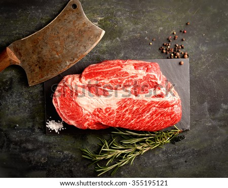 raw veal steak marbled basalt, a knife for meat, rosemary on a dark background - stock photo