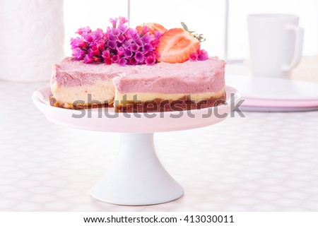 Raw vegan strawberry or raspberry cheesecake gluten-free on a white decorate table  background, Vegan Paleo Diet Cheesecake  with Dates and Cashews with plate and pink cup of tea,  Horizontal - stock photo