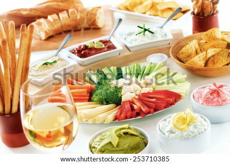 Raw vegetable and dips buffet display, arranged with wine, bread and snacks  - stock photo