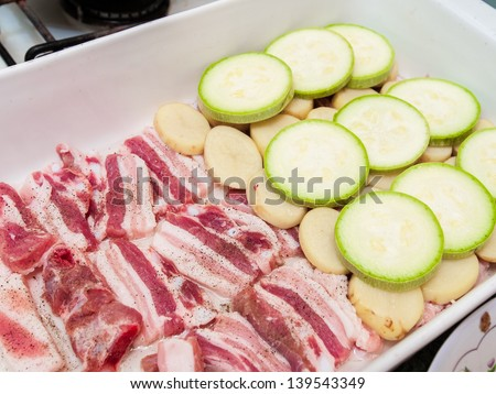 Raw vegetables and bacon prepared for roasting - stock photo