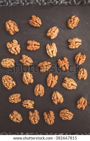 Raw walnut pieces laid on a black background - stock photo