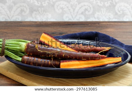 Raw, washed purple carrots on an oval plate.  Whole and sliced carrots to show details. - stock photo