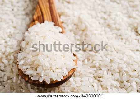 Raw white rice in a wooden spoon. Selective focus. - stock photo