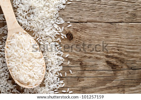 Raw white rice in spoon on wooden background - stock photo