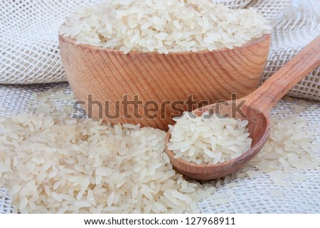 Raw white rice in wooden bowl and spoon on burlap, food ingredient photo - stock photo