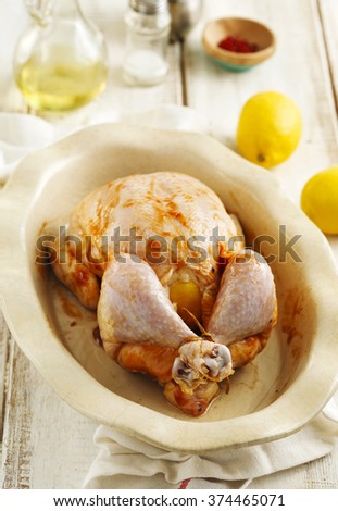 Raw whole chicken stuffed lemon and spices preparing for cooking - stock photo