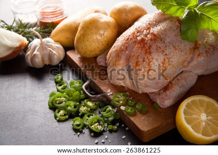 raw whole chicken with potatoes - stock photo