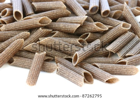 Raw wholegrain pasta scattered on white background - stock photo