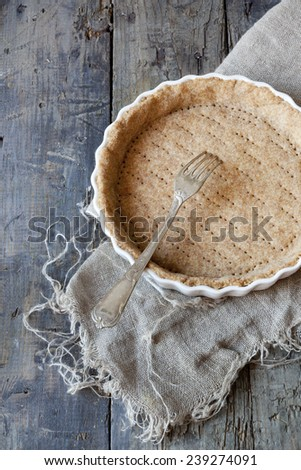 raw wholemeal dough for tart on ceramic mold for quiche on wooden table with fork - stock photo