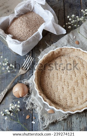 raw wholemeal dough for tart on ceramic mold for quiche with eggs and flour on table with flowers and fork - stock photo