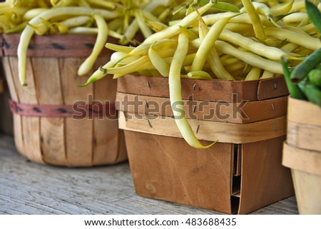 raw yellow beans in wooden bushel basket and produce box at the farmer's market