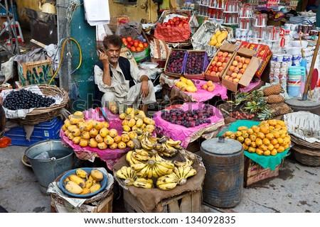 RAWALPINDI, PAKISTAN - JULY 16: Unidentified Pakistani man sells fresh fruits at Raja Bazaar on July 16, 2011 in Rawalpindi, Pakistan. Raja Bazaar is the main tourist attraction in Rawalpindi. - stock photo