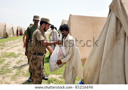 RAWALPINDI, PAKISTAN - SEPT 23: Army soldiers distribute relief goods among flood affectees at a relief camp established at a flood hit area of Sindh province on September 23, 2011 in Rawalpindi.