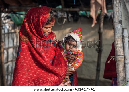 RAXAUL, INDIA - NOV 12: Unidentified Indian woman with her child on Nov 12, 2013 in Raxaul, Bihar state, India. Bihar is one of the poorest states in India. The per capita income is about 300 dollars.