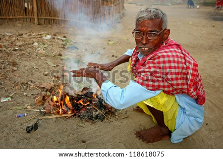 RAXAUL - NOV 2: Indian man heating himself at the fire on Nov 2, 2011 in Raxaul, Bihar state, India. Bihar is one of the poorest states in India. The per capita income is about 115 dollars.