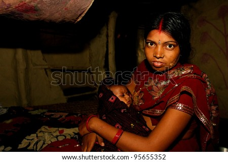 RAXAUL - OCTOBER 25: Young Indian mother with sleeping child on October 25, 2011 in Raxaul, Bihar state, India. Bihar is one of the poorest states in India. The per capita income is about 115 dollars. - stock photo