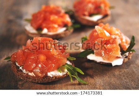 ray bread with cream cheese and smoked salmon on wooden background - stock photo