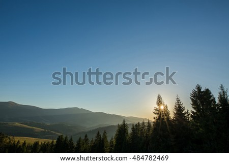 Ray of sunlight at sunset shining through the fog. The mountains. Forest.