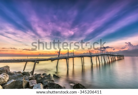 Ray sunrise on a wooden bridge with pink rays emitted before sunrise beside the wooden bridge with smooth water makes sunrise more lively and more beautiful - stock photo