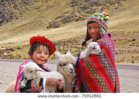 RAYA PASS, PUNO - NOVEMBER 22: Unidentified children in traditional clothing play with their animals on November 22, 2010 in Raya Pass, Puno, Peru. - stock photo