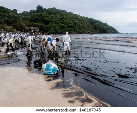 RAYONG -JUL 31: Oil stain in the water of Aou Prow beach, Rayong, Thailand on Jul 31, 2013. The disaster came from leaked oil from the oil tanker unloading in the sea on July 27. - stock photo