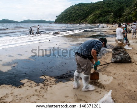 RAYONG -JUL 31: People clearing contaminated sand at the Aou Prow beach, Rayong, Thailand on Jul 31, 2013. The spilled oil came from the accidental leaking during oil tanker transferring on July 27.  - stock photo